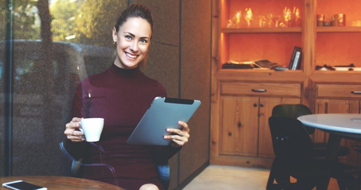 Colaboradora completando una encuesta de recursos humanos mientras toma un café
