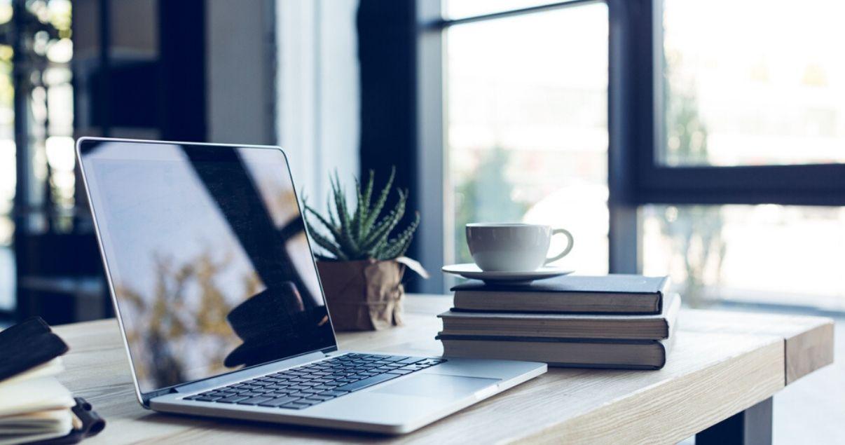 Computadora portátil y libros sobre un escritorio en una casa durante home office